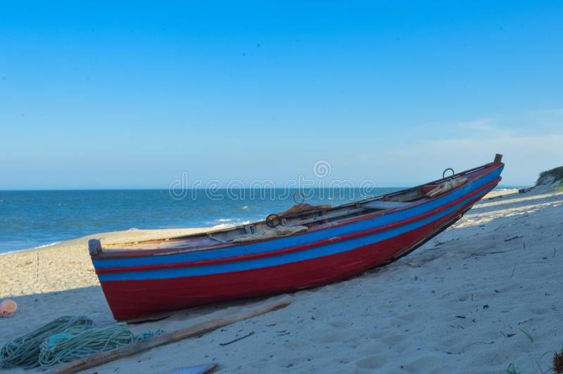 Colorful Boat at Macaneta beach in Maputo Mozambique. Red and blue colors. An aggressive , clean and beautiful Maputo beach royalty free stock photography