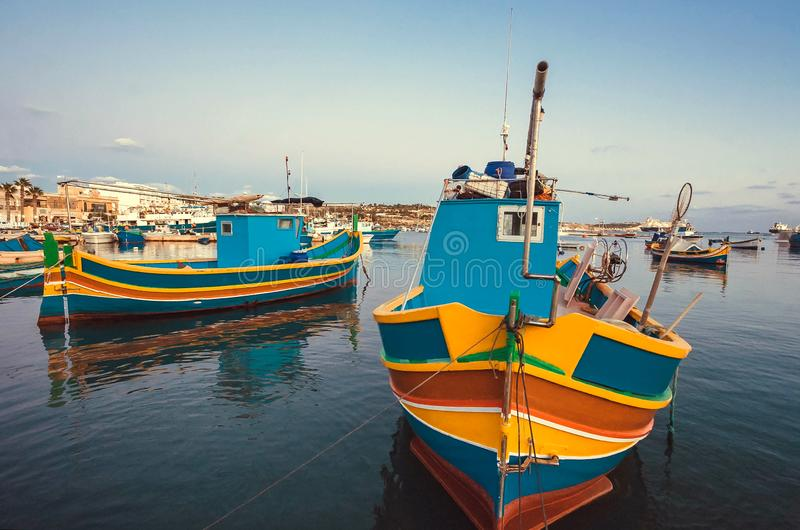 Colorful boats of fishermen in harbor of Malta. Evening over small Mediterranean town royalty free stock photography