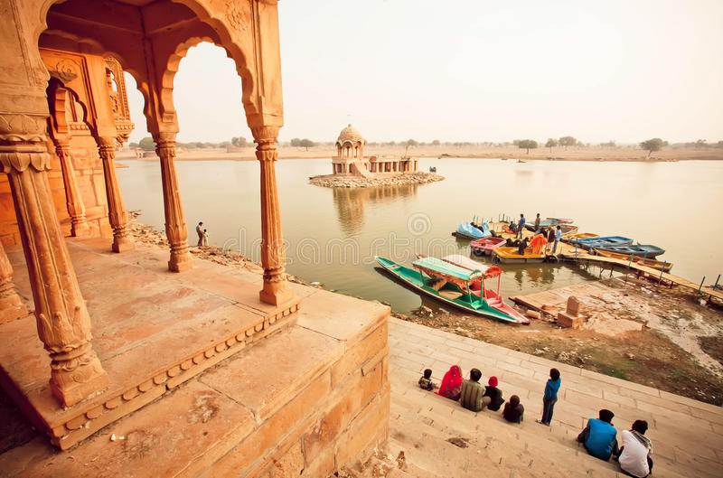 Colorful boats on indian river and group of tourists having rest near water. JAISALMER, INDIA - FEB 2: Colorful boats on indian river and group of tourists royalty free stock photo