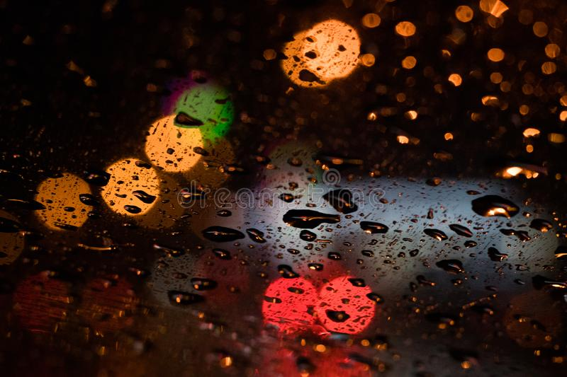 Colorful bokeh shot traffic lights and rain through the glass. Abstract royalty free stock images