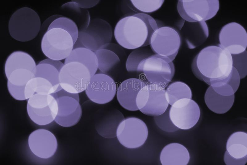 Colorful bokeh ultra violet. Coloured bokeh Christmas tree garlands Christmas lights, photo is toned in ultra violet stock images