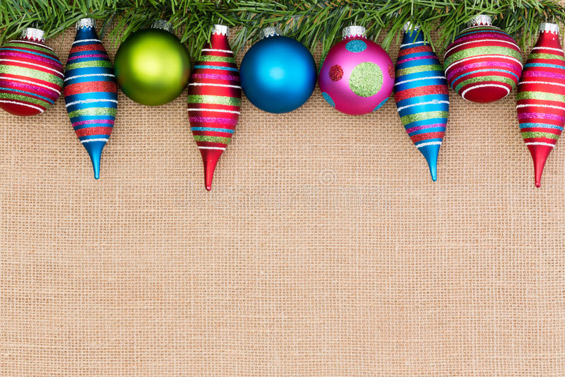 Colorful border of Christmas tree ornaments. With baubles and spindles nestling on green pine foliage over a hessian or burlap background with copy space stock photos