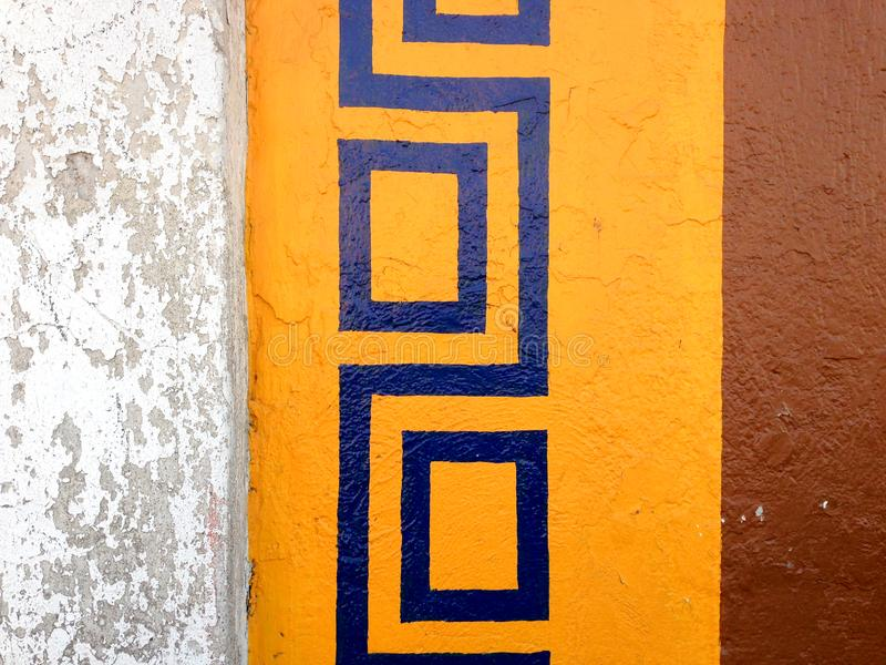 Colorful border painted on an exterior wall. Colorful repeat pattern border painted on an exterior wall with a blue motif over a yellow frame with brown paint stock image