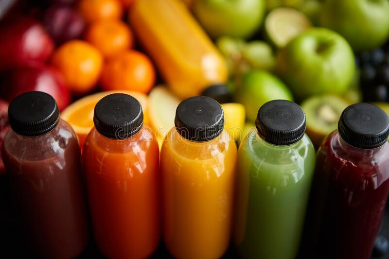 Colorful bottles filled with fresh fruit and vegetable juice or smoothie stock images