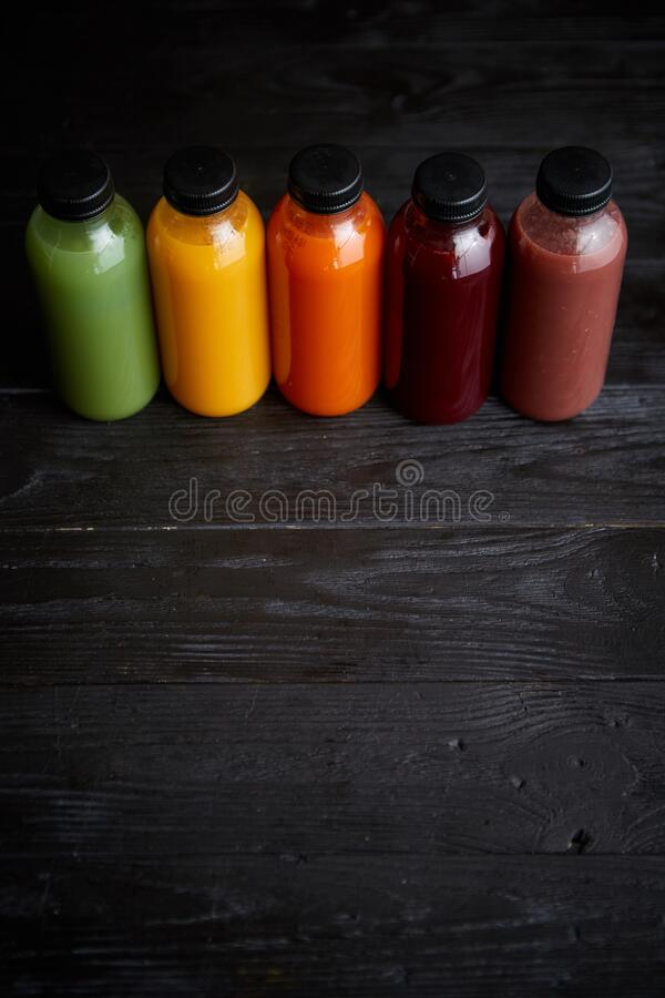 Colorful bottles filled with fresh fruit and vegetable juice or smoothie royalty free stock images