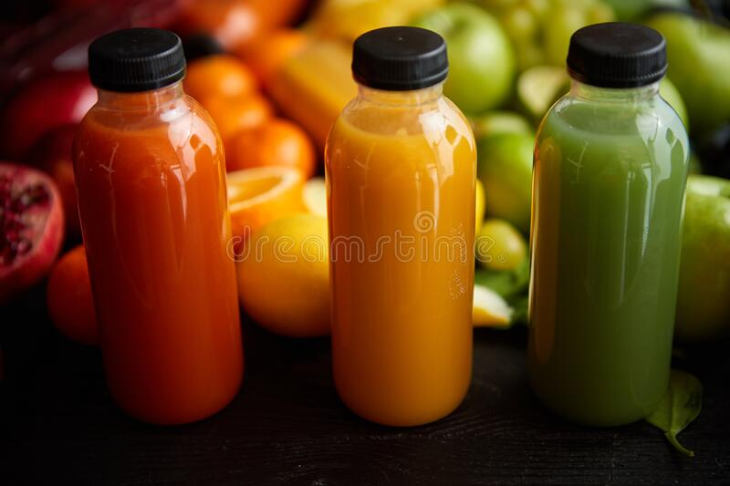 Colorful bottles filled with fresh fruit and vegetable juice or smoothie royalty free stock image