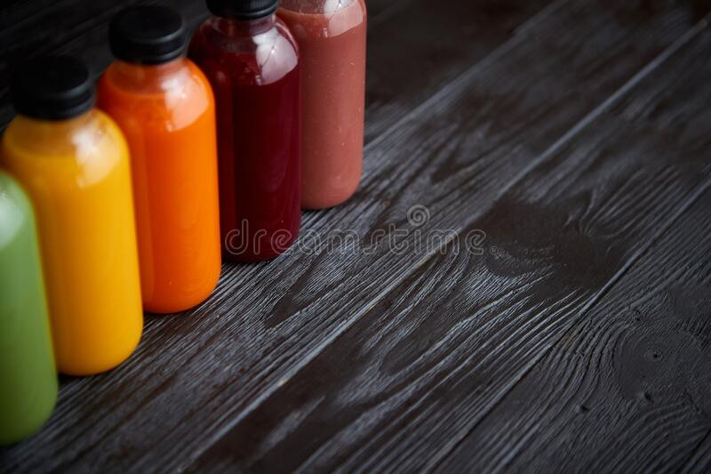 Colorful bottles filled with fresh fruit and vegetable juice or smoothie stock image