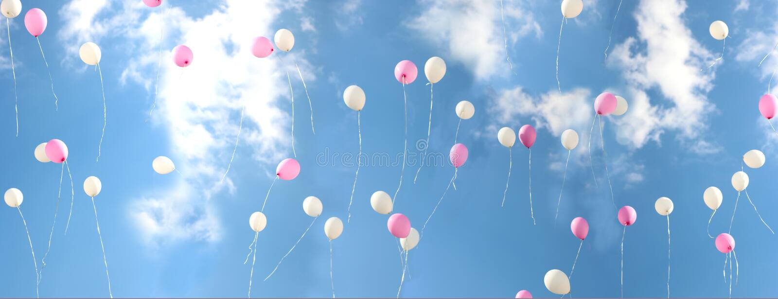 Colorful bouncing balls outdoors against blue sunny sky. Banner stock photos