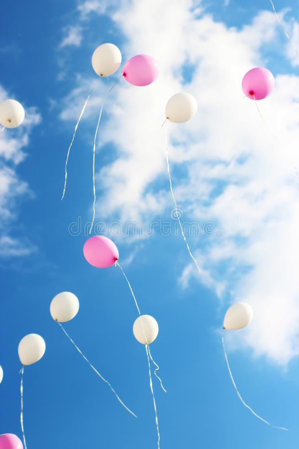 Colorful bouncing balls outdoors against blue sunny sky. /pink and white balls royalty free stock photos