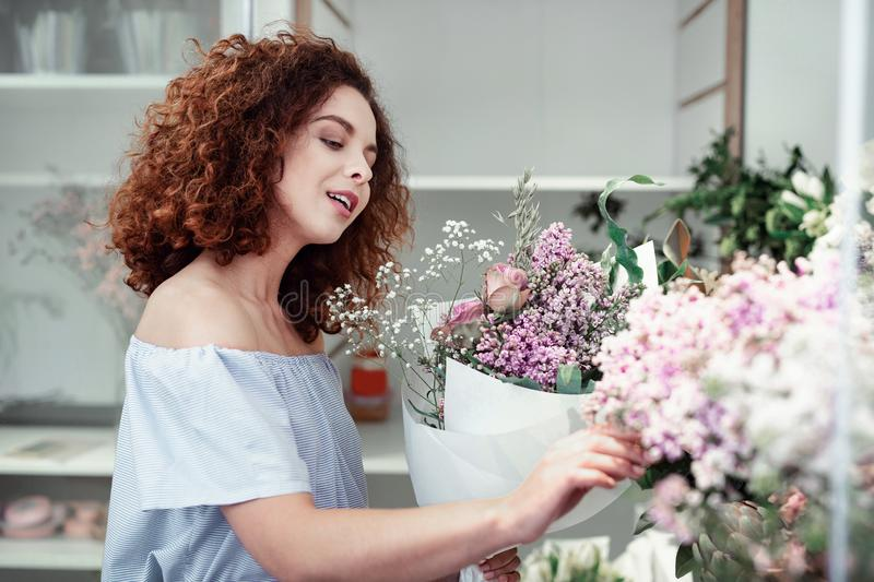 Attractive curly-haired young florist choosing extra flowers for her bouquets stock image