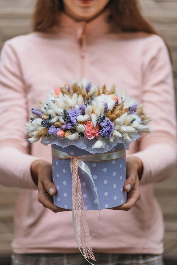 Colorful bouquet of different dried flowers deadwood flowers in the hands of florist woman. Rustic flower background stock photo