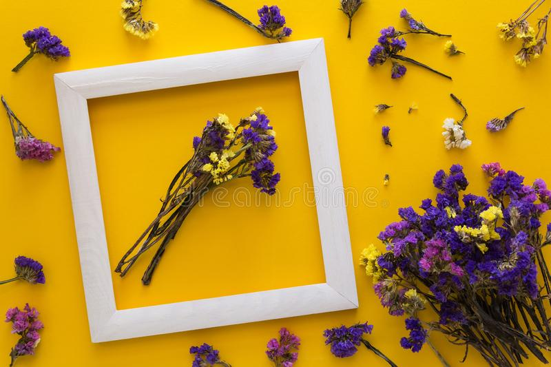 Colorful bouquet of dried autumn flowers lying on a white frame on yellow paper background. Copy space. Flat lay. Top view. royalty free stock image