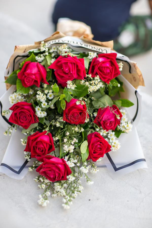 Colorful bouquet of fresh flowers against brick wall. close up of red roses royalty free stock photography