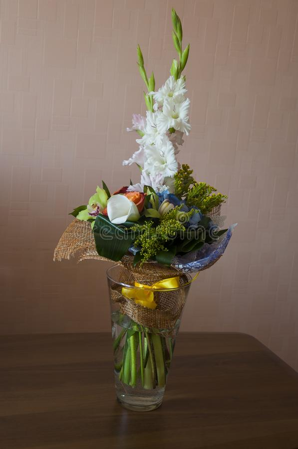 Colorful bouquet with such flowers as gladiolus, orchid, roses, callas, mimosa are standing in the big glasses vase. Tints of whit stock image