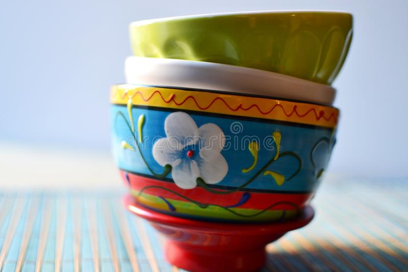 Colorful bowls. Stacked bowls of different colors on a kitchen table, front close-up view royalty free stock photo