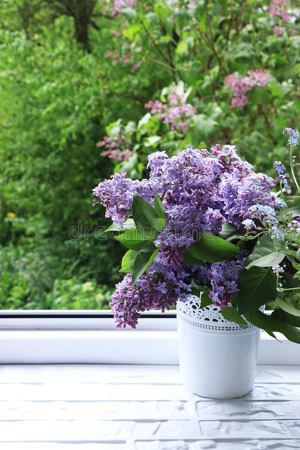 Colorful branches of lilac on an open window with a view of a blossoming lilac. A lilac bouquet in a vase against a background of green trees after rain in May stock photo