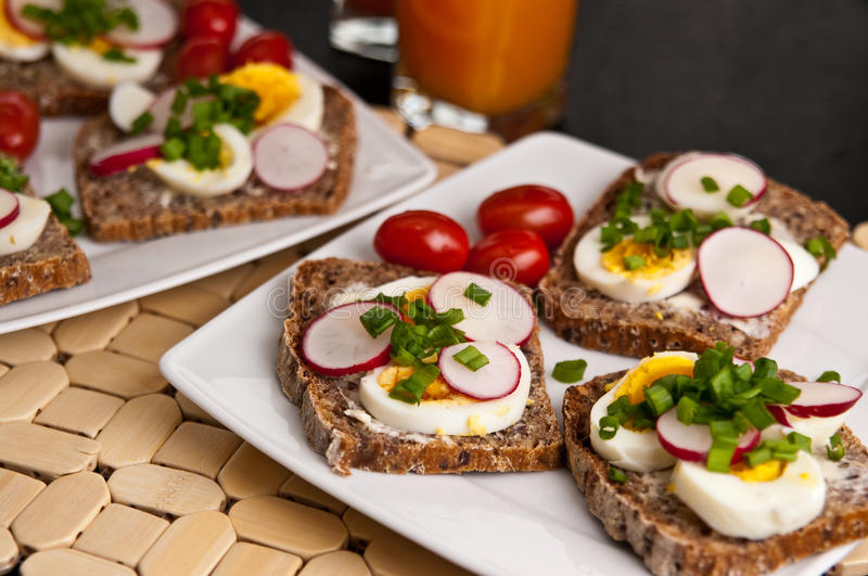 Colorful breakfast sandwiches. With homemade wholegrain bread, boiled eggs, spring onion and sliced radish royalty free stock images