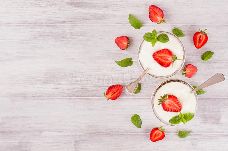 Colorful breakfast with sliced strawberry, leaves mint in jars on white wood board, top view. Colorful breakfast with sliced strawberry, leaves mint in jars on stock image