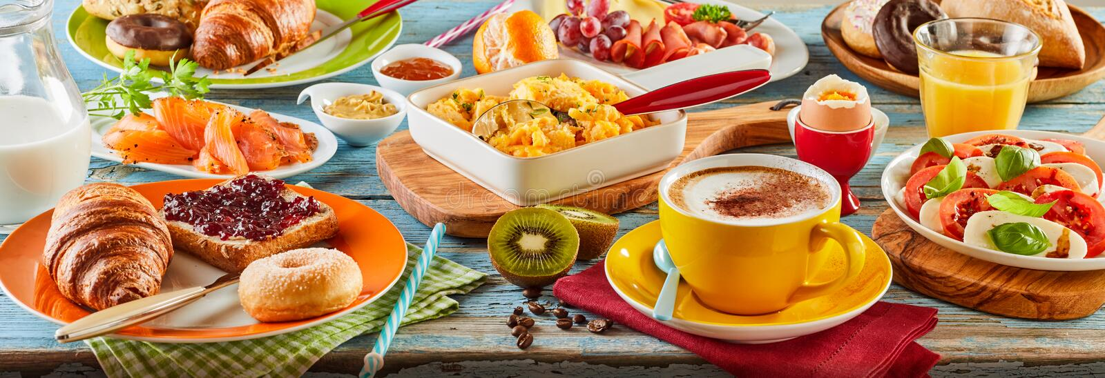 Colorful breakfast spread in a panoramic banner. With smoked salmon, Caprese salad, scrambled and boiled egg, meat cheese donut, toast and jam, orange juice and stock image