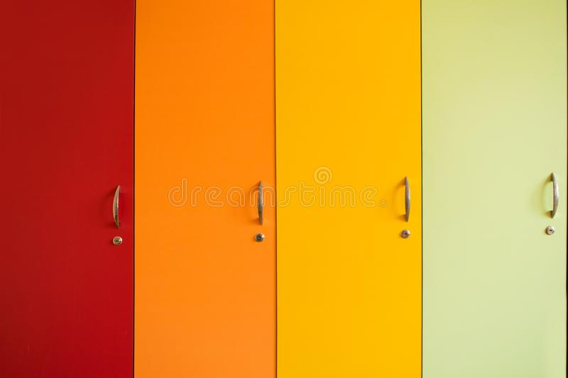 Colorful bright doors of cabinets with handles. Rainbow furniture in kindergarten or school. Bright background of yellow. Orange, red and green stock photo