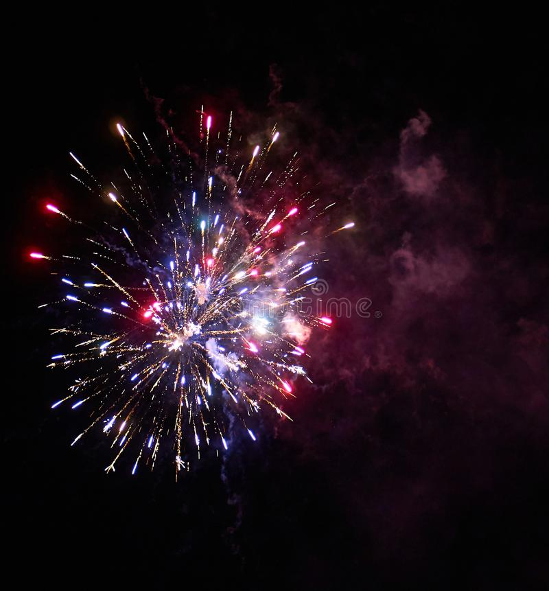 Colorful bright red and blue fireworks and smoke in the night sky background stock photography