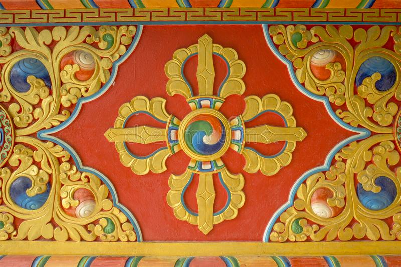 A colorful bright red yellow blue Buddhist vajra image on the wall of the temple. sacred images. Colorful bright red yellow blue Buddhist vajra image on the wall stock photography