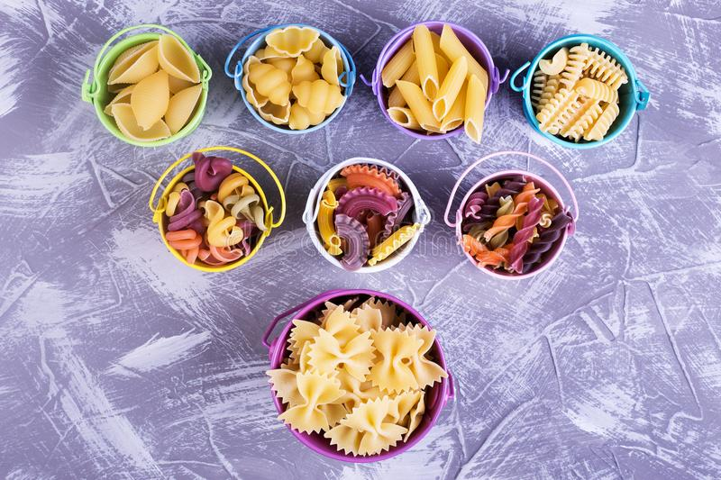 Colorful buckets with different pasta. Funny colored buckets with different kinds of pasta. Beautiful still life with Italian pasta royalty free stock photos