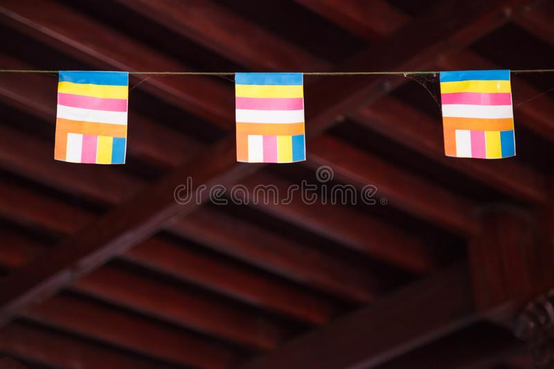 Colorful Buddhist flag in Buddhist temple with blank wooden ceiling background. Sign and Symbol of Worship, Belief, Culture, royalty free stock image