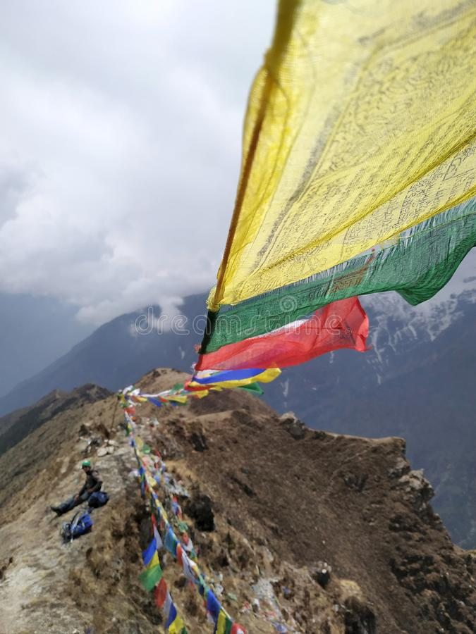 Colorful prayer flags waving against a cloudy sky in mountains stock photography