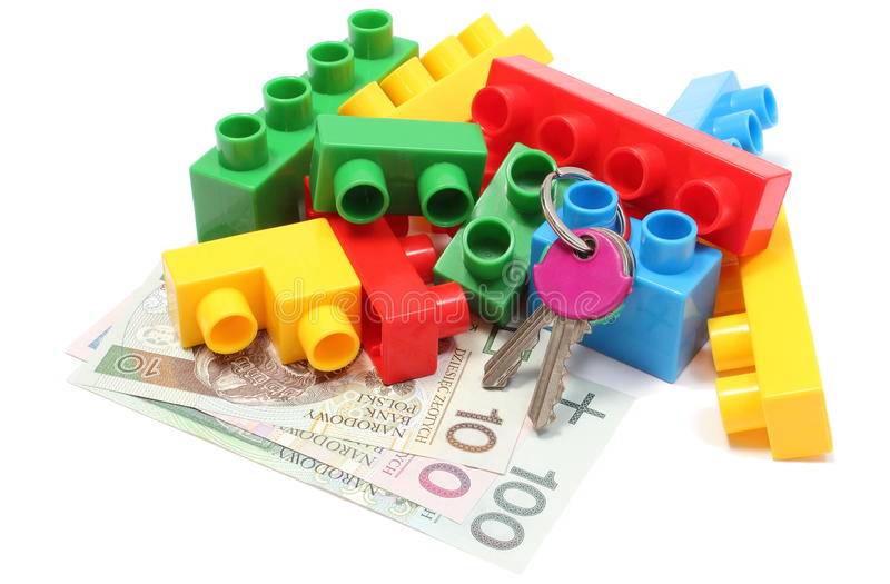Colorful building blocks for children with home keys and money. Closeup of home keys, heap of colorful building blocks and banknotes, building blocks for royalty free stock image