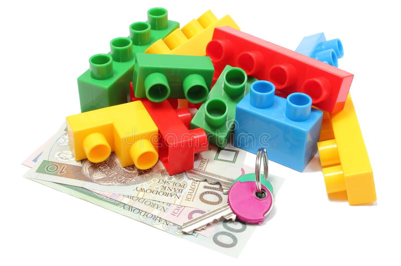 Colorful building blocks for children with home keys and money. Closeup of home keys, heap of colorful building blocks and banknotes, building blocks for stock images