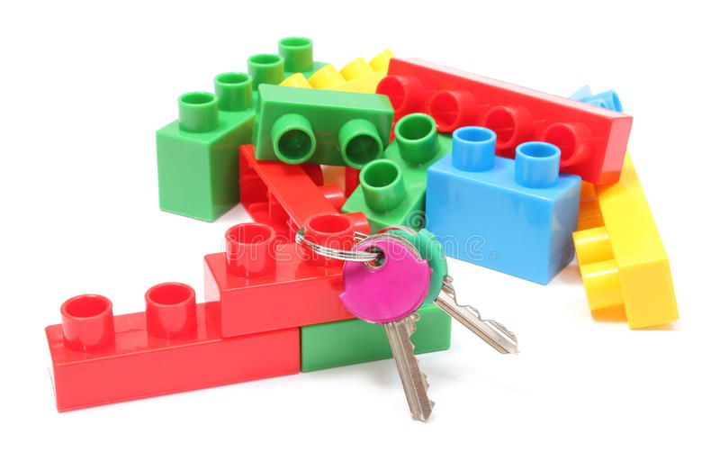 Colorful building blocks for children with home keys on white background. Closeup of home keys and heap of colorful building blocks, building blocks for children royalty free stock image
