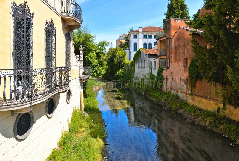 Colorful buildings, architecture, water reflections on city canal and old facade with blue sky in Padua Veneto, italy. Padova royalty free stock image