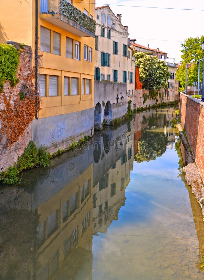 Colorful buildings, architecture, water reflections on city canal and old facade with blue sky in Padua Veneto, italy. Padova royalty free stock photo