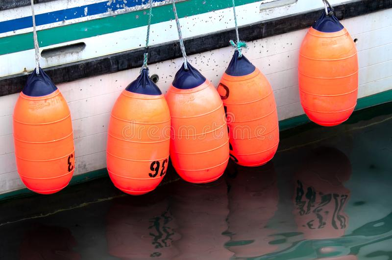 Colorful buoys on the side of a fishing boat. Colorful orange and blue buoys hang over the side of an old fishing boat in the harbor in Seldovia, Alaska stock photo