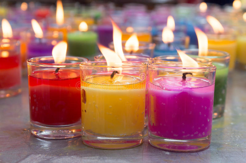 Colorful burning candles. And wax stock photo