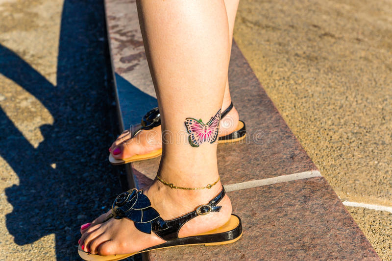 Colorful butterfly tattoo on ankle. Colorful butterfly tattoo on girls ankle stock image