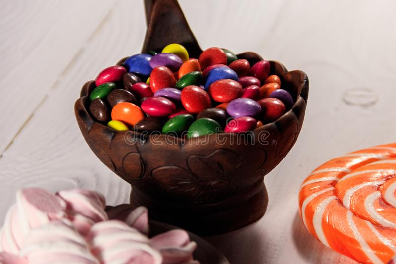 Colorful button shaped candies filled with chocolate in ceramic bowl royalty free stock photography
