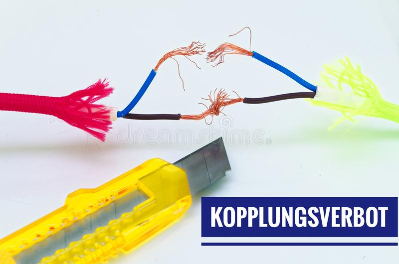 Colorful cables that were patched separately and makeshift and a craft knife with inscription in German Kopplungsverbot in English. Coupling ban royalty free stock photography