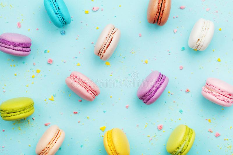 Colorful cake macaron or macaroon on turquoise pastel background from above. French almond cookies on dessert top view. stock photo
