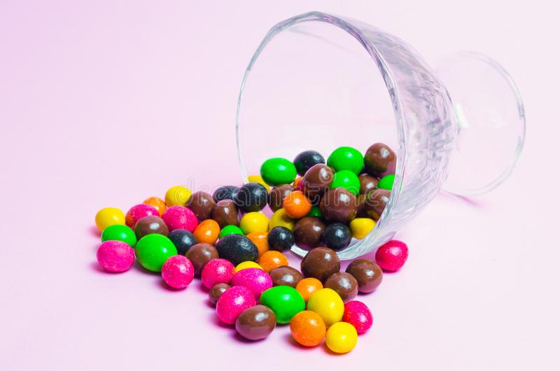 Colorful candies in a glass vase on a pink background, sweets. place for text stock photography