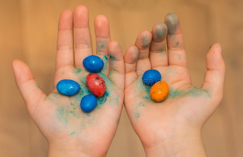 Colorful candies held in child hands. The hands are dirtywith the color of the candy stock photos