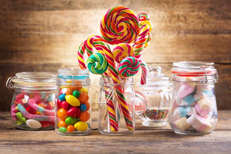 Colorful candies, jellies, lollipops, marshmallows and marmalade. In a glass jars on wooden table stock image