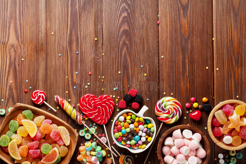 Colorful candies, jelly and marmalade. On wooden background. Top view with copy space royalty free stock images