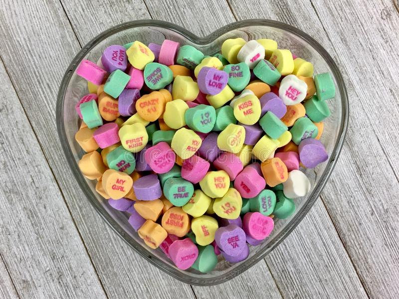 Candy hearts in a heart shaped bowl royalty free stock image