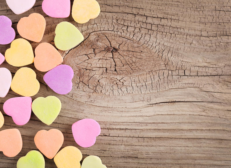 Colorful candy hearts on wooden background. Colorful candy hearts on wood background royalty free stock photography