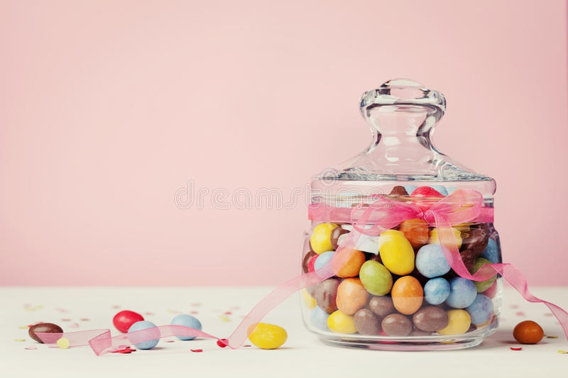Colorful candy jar decorated with bow ribbon against pink background. Gifts for Birthday or Easter stock image