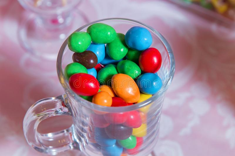 Colorful candy . Multi colored sweets . Colored candy in a glass . Round chocolate is very colorful stock images