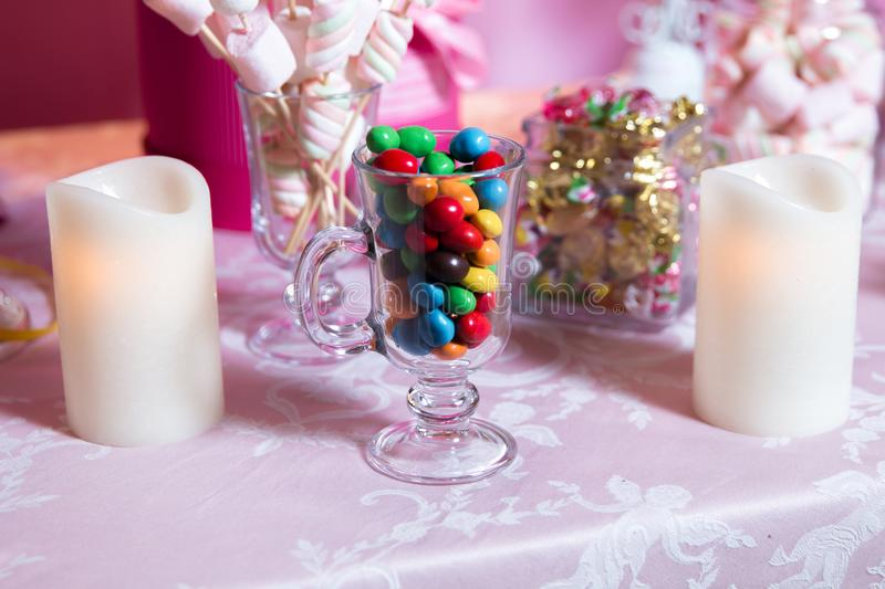 Colorful candy . Multi colored sweets . Colored candy in a glass . Round chocolate is very colorful . Candle . royalty free stock photography