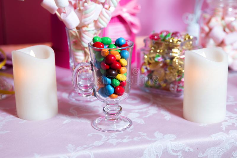 Colorful candy . Multi colored sweets . Colored candy in a glass . Round chocolate is very colorful . Candle . stock photography